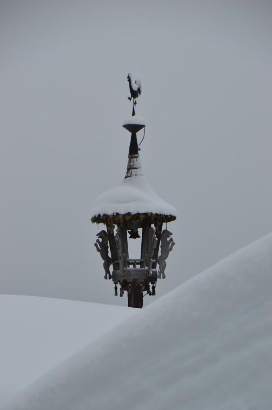 glocke verschneites dach königsleiten