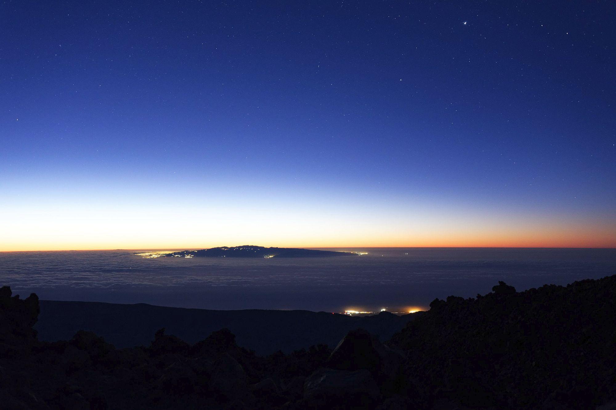 Die Sonne steht knapp unter dem Horizont im Osten. Der Blick auf das Wolkenumgebene Gran Canaria vom Pico del Teide erlaubt auch noch die letzten Sterne zu beobachten bevor die Sonne alles überstrahlt.