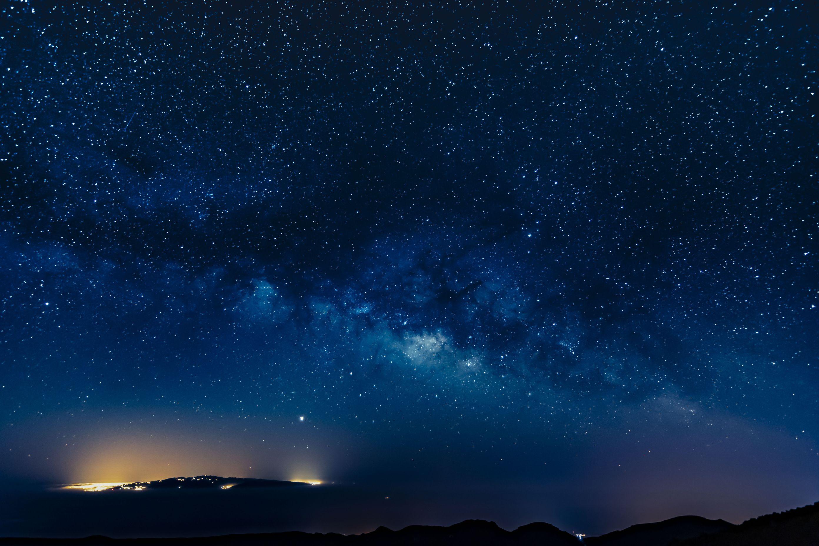 Die Milchstraße steht hoch über dem Pico del Teide und im Hintergrund taucht Gran Canaria durch die Wolkendecke auf